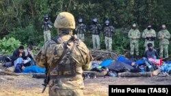 Группа мигрантов и пограничники на участке польско-белорусской границы