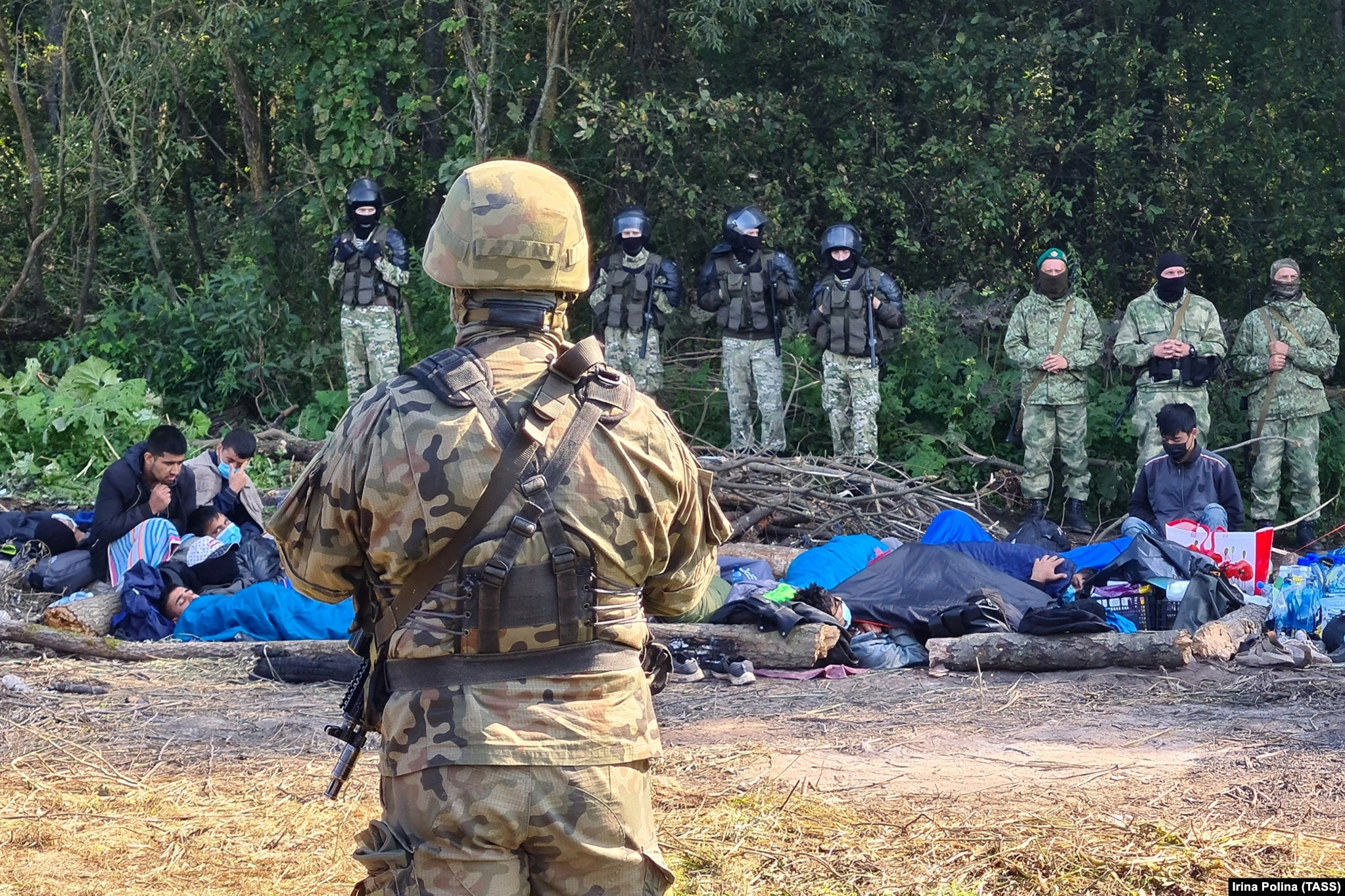 The group of migrants, photographed between an armed Polish serviceman (in foreground) and Belarusian police. The standoff comes amid a surge in mostly Middle Eastern migrants entering the EU illegally from Belarus. European authorities accuse Minsk of deliberately engineering the crisis as a reaction to sanctions imposed by the EU since Belarusian strongman Alyaksandr Lukashenka's crackdown began following a disputed election one year ago.