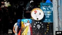 Үкіметке наразылық акциясы кезінде полицияға қарсылық танытушылар. Каракас, Венесуэла, 12 маусым 2017 жыл. (Көрнекі сурет.)