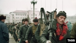 Chechen fighters head out of Grozny to fight Russian federal forces in December 1994.