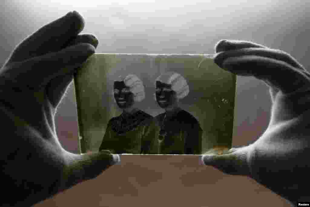 """A museographer holds a glass plate negative from the """"Costica Acsinte picture archive"""" at Ialomita county museum in Slobozia. (Reuters/Bogdan Cristel)"""