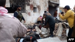 A handout picture released by the Syrian opposition Shaam News Network allegedly showing Syrians helping victims following an air strike by regime forces near a bakery in the rebel-held town of Halfaya in the central province of Hama on December 23.