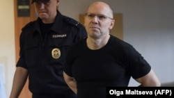 Russian journalist Igor Rudnikov is led to court in Kaliningrad on June 17.