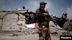 Представник афганських сил безпеки стоїть перед зруйнованою будівлею, ілюстративне фото