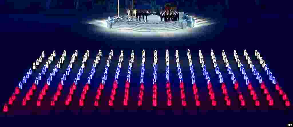Athlete marshals with LED elements in their costumes create the colours of the Russian flag.
