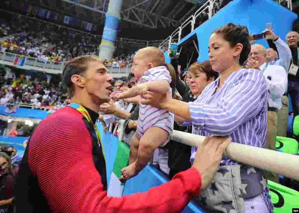 Плавець зі США Майкл Фелпс (л) із нареченою Ніколь Джонсон (п) і їхнім сином Бумером (с) після того, як він здобув золоту медаль у змаганні чоловіків із плавання батерфляєм на 200 метрів.