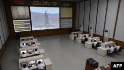 Technicians watch live images of the rocket Unha-3 at the satellite control room of the space center on the outskirts of Pyongyang.