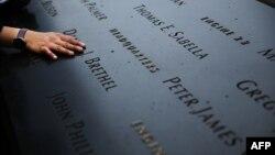 Жінка кладе руку на вигравірувані імена загиблих від терактів 11 вересня, Меморіальний музей жертв, Нью-Йорк, 2014 рік