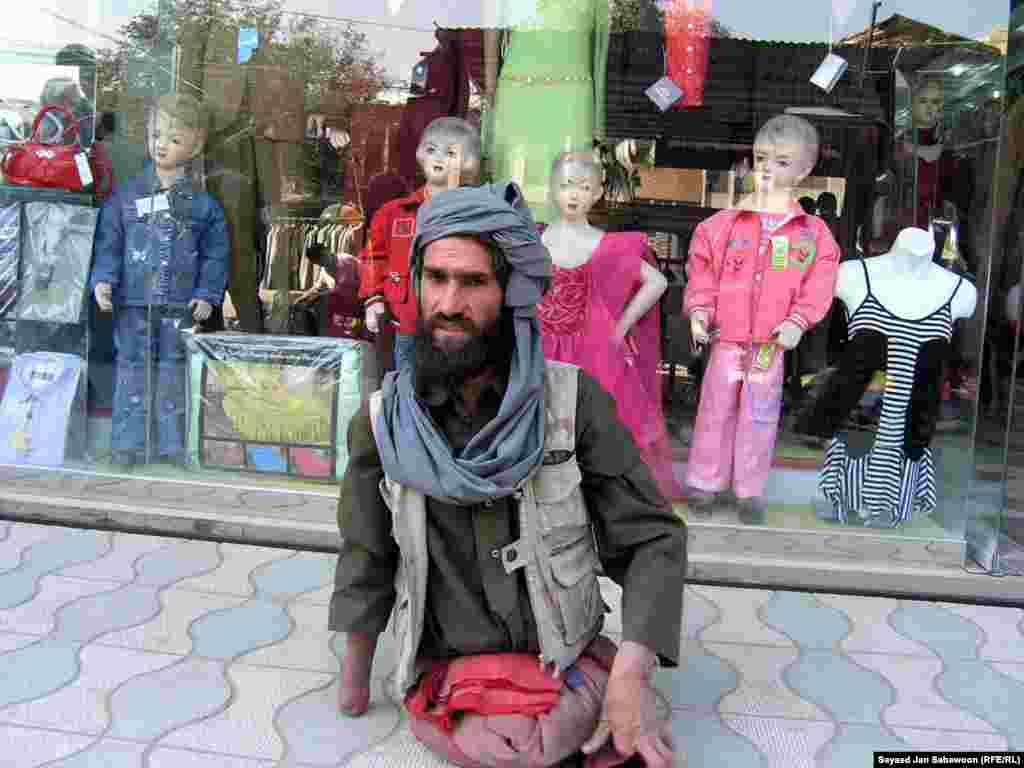 A disabled man begs in front of the market in Kabul.
