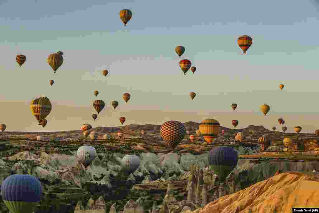 Hot-air balloons carrying tourists rise into the sky at sunrise in Cappadocia, Turkey. (AP/Emrah Gurel)
