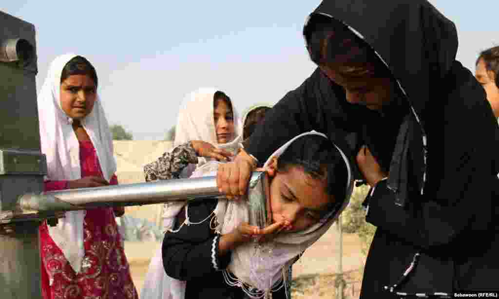 Afghan children drink water on the outskirts of Jalalabad.