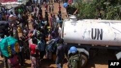 Военные японского контингента ООН раздают воду беженцам на базе в окрестностях столицы Южного Судана Джубы, 16 декабря 2013 года.