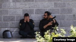A member of the Iranian security forces reacts during a pause in the response to the Islamic State attack on the Iranian parliament.