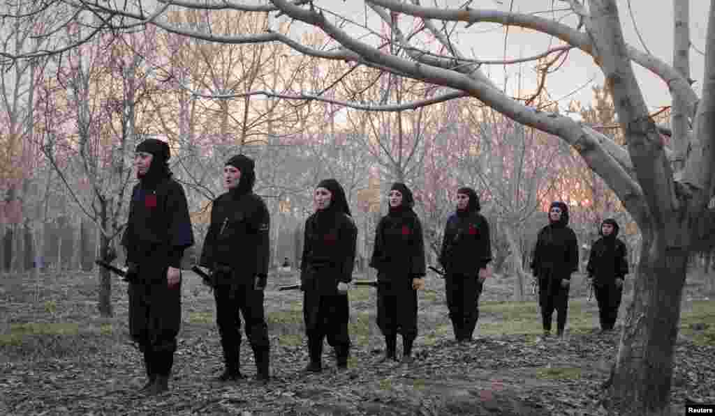 Ninjutsu practitioners prepare for a sword drill in a park in Karaj.