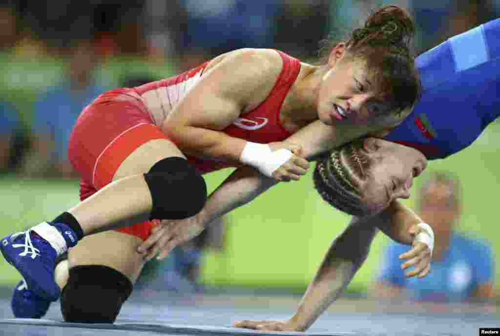 Eri Tosaka of Japan (left) and Maria Stadnik of Azerbaijan compete in the women's wrestling freestyle 48-kilogram final.