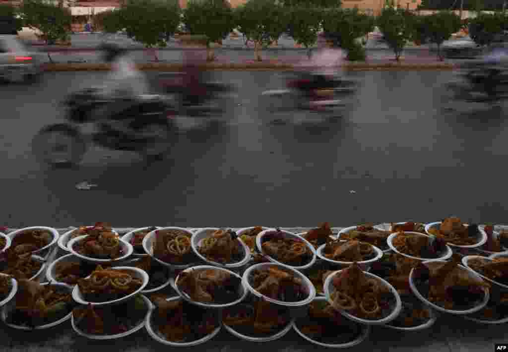 Motorcyclists ride past plates of Iftar foods placed for residents to break their Ramadan fast along a street in Karachi, Pakistan. (AFP/Asif Hassan)