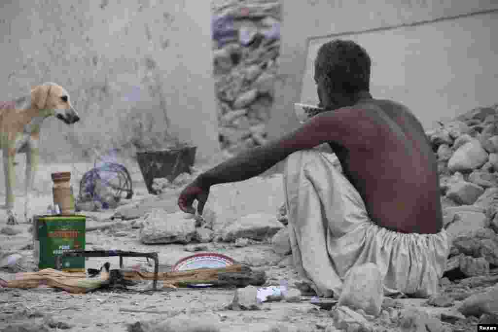 An earthquake survivor sits and drinks tea on the rubble of a mud house in Awaran.