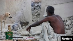 An Awaran man drinks tea as he sits in what remains of his house.