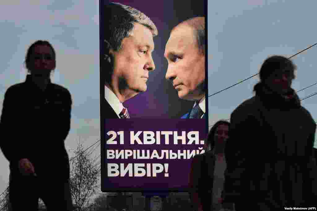 People in Kyiv walk past an election-campaign poster showing the current Ukrainian President Petro Poroshenko facing Russian President Vladimir Putin. (AFP/Vasily Maximov)