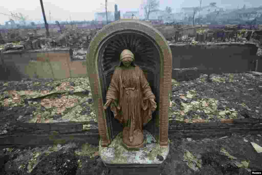 A statue is seen among homes devastated by fire and the effects of Hurricane Sandy in the Breezy Point section of the Queens borough of New York.