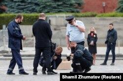 Poliția rusă, cercetând pistolul folosit de Pavel Krisevici în timpul acțiunii sale de protest din Piața Roșie, 11 iunie 2021