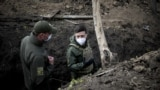 Volodimir Zelenszkij ukrán elnök egy tiszt társaságában sétál egy lövészárokban. Az elnök a donyecki régióban fekvő Petrivszke falu közelében állomásozó ukrán katonai egységhez látogatott el, 2020. április 11-én.