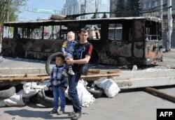 Краматорск қаласында өртенген троллейбус қаңқасы жанында балалармен бірге тұрған ер адам. Украина, 4 мамыр 2014 жыл.