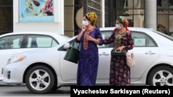 Turkmen women wear protective face masks as a preventive measure against the spread of COVID-19 in Ashgabat.