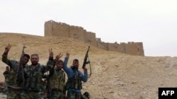 Syrian pro-governement forces gesture next to the Palmyra citadel during a military operation to retake the ancient city from the extremist Islamic State group.