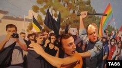 Одна из картин Алтунина с прорезями для голов изображает преследование полицией гомосексуалистов. Санкт-Петербург, 23 августа 2013 года.