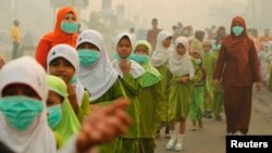 "Students wear masks as they celebrate ""Khatam"" in haze-hit Dumai, in Indonesia's Riau province in June 2013."