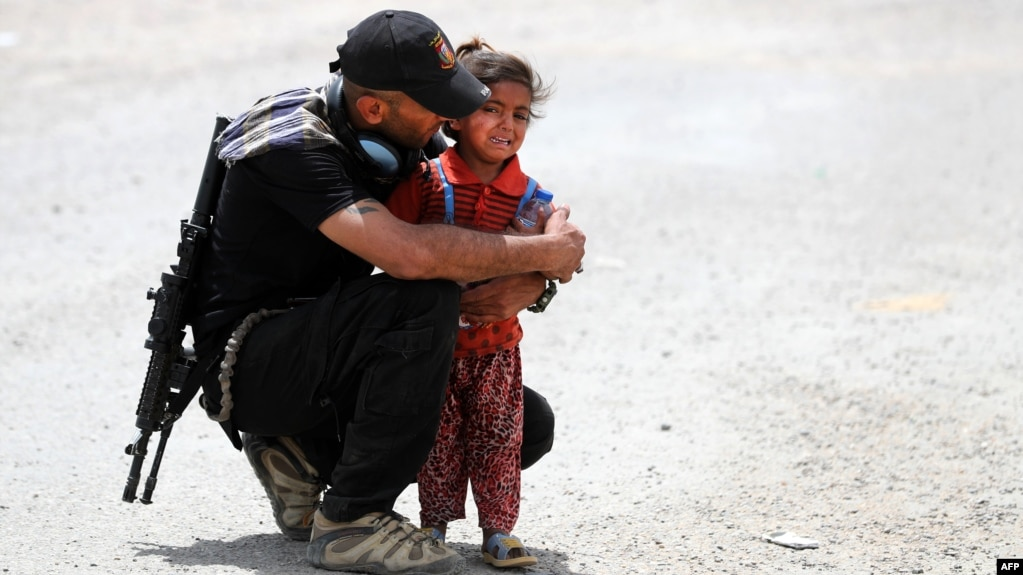 An Iraqi soldier helps a displaced girl near Mosul.