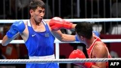 Казахстанский боксер Асланбек Шымбергенов (в синем) в бою против Сарохоту Лумбатоби из Индонезии. Джакарта, 24 августа 2018 года.