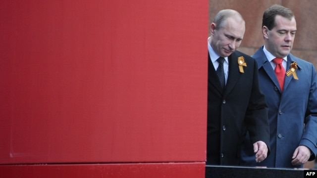Russian President Vladimir Putin (left) and Prime Minister Dmitry Medvedev arrive to watch Victory Day parade at Red Square in Moscow on May 9.