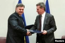 Едуард Ставицький потискує руку єврокомісару з енергетики Гюнтеру Еттінгеру (праворуч) після підписання угоди про співпрацю в енергетичній сфері на саміті Україна-ЄС у Брюсселі, 25 лютого 2013