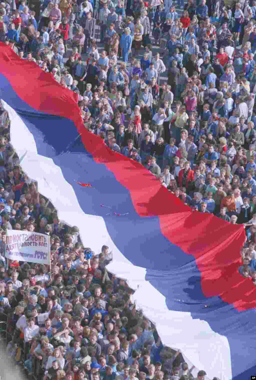 Тисячі радісних москвичів влаштували мітинг на Червоній площі в Москві, 22 серпня 1991 року. Велетенський російський триколор сповіщає про провал державного перевороту.