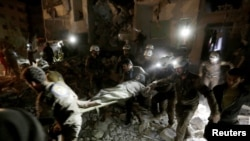 Спасатели несут выжившую в районе авиаударов, нанесенных, предположительно, российской авиацией. Идлиб, 31 мая 2016 года.