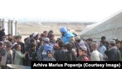 Militarul român Marius Popența în mijlocul unui grup de copii afgani. Poartă echipament de protecție albastru al personalului ONU