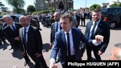 Прэзыдэнт Францыі Эманюэль Макрон (у цэнтры) паціскае рукі выбарнікам пасьля галасаваньня на першым туры парлямэнцкіх выбараў. Лё-Туке, поўнач Францыі, 11 чэрвеня 2017 году