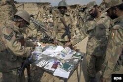 پاکستاني پوځیان په جنوبي وزیرستان کې د عملیاتو پر وخت د مشکوکو وسله والو پاسپورټونه او نور اسناد ښيي. د ۲۰۰۹ز د اکتوبر ۲۹مې انځور.