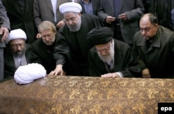 Iran's Supreme Leader Ayatollah Ali Khamenei (second from right) and Iranian President Hassan Rohani (center) pray on Rafsanjani's coffin before his funeral ceremony in Tehran on January 10.