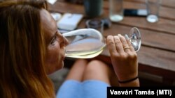 Fehérbort iszik egy vendég egy pincészet teraszán Csopakon, 2020. július 21-én