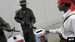 A political activist approaches mock ballot boxes as colleagues dressed as Myanmar soldiers raise their rifles during a mock vote as part of a protest outside the Myanmar Embassy in Bangkok today.