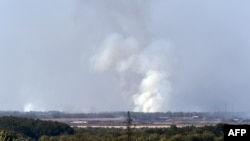 Smoke rises after a weapons factory controlled by pro-Russian militants exploded near Donetsk on September 20.