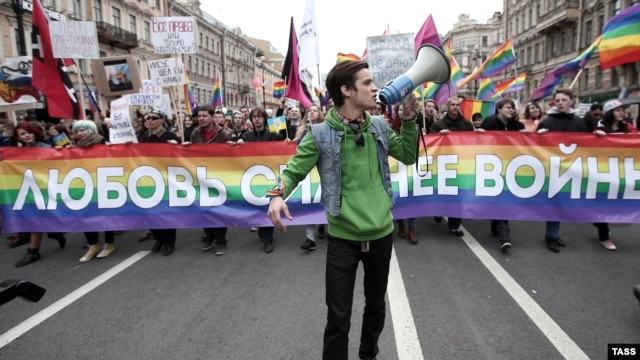 """LGBT activists carrying a banner reading """"Love Is Stronger Than War"""" in 2014. Russia has moved to ban transgender people from having driver's licenses."""