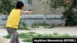 Мальчик играет в войну близ здания, где проходит суд по делу о расстреле демонстрантов в Жанаозене. Актау, 7 мая 2012 года.