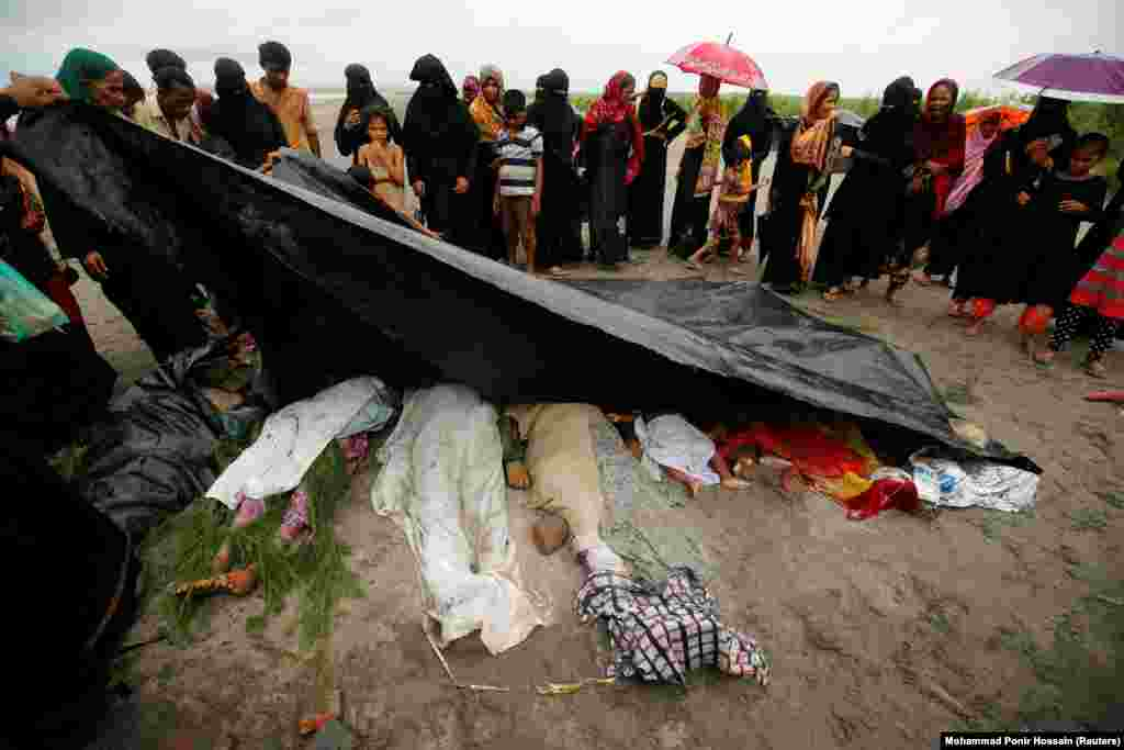 People cover the bodies of Rohingya women and children who died after their boat capsized while crossing the Bay of Bengal, near Teknaf, Bangladesh.