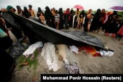 Толпа на берегу реки в Бангладеш смотрит на тела беженцев-рохинджа, утонувших ночью при переправе. 1 сентября