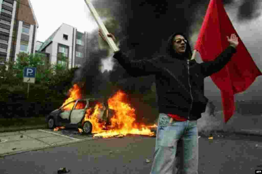 یک جوان شورشی، در برابر خودرویی که سوخته در حال شعار دادن