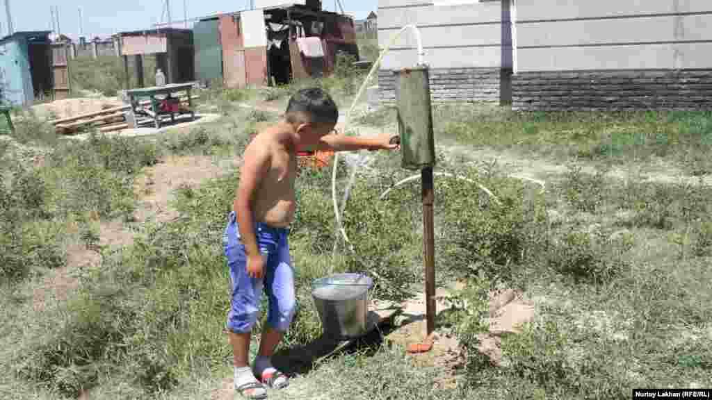 Мальчик таскает воду из выкопанного вручную колодца во дворе в дом своей бабушки. Во многие села близ Алматы, такие как Жалгамыс и Жанакурылыс, не проведены водопровод и газ.